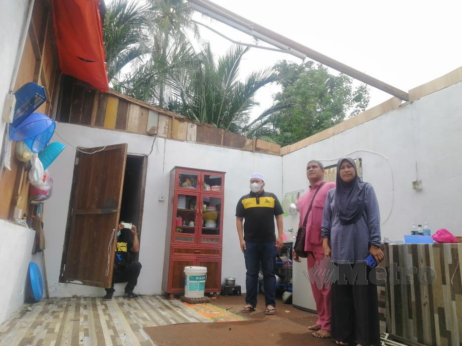 SUZILAWATI (kanan) bersama suami menunjukkan keadaan rumah mereka yang dilanda ribut awal pagi tadi. FOTO SHAIFUL SHAHRIN AHMAD PAUZI