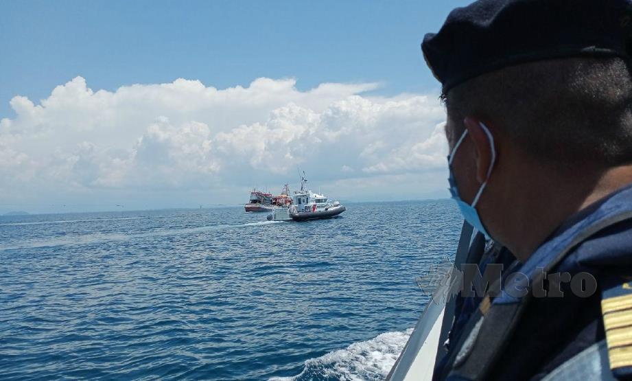 MUHD Nur Syam Asmawie melihat Kapal Penyelamat 7 milik APMM yang mengiring dua bot nelayan asing Vietnam yang ditahan di perairan Tok Bali, Pasir Puteh, hari ini. FOTO NOR AMALINA ALIAS