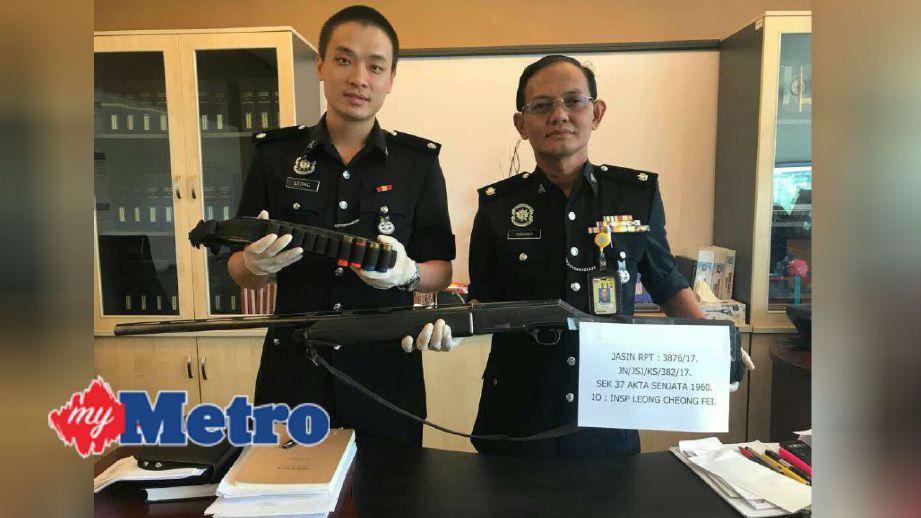 Arshad (kanan) menunjukkan senapang yang dirampas. FOTO ihsan polis