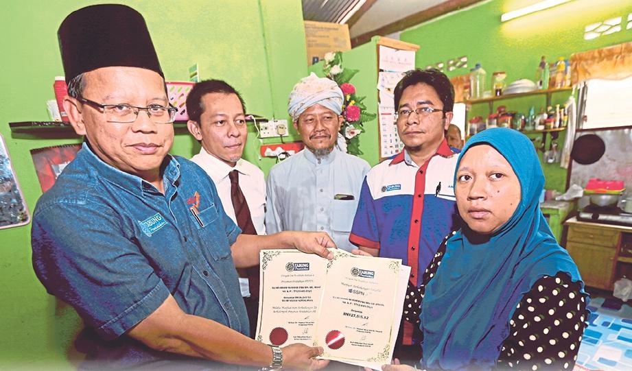 ABDUL Ghaffar (kiri) menyampaikan sijil Manfaat Perlindungan Takaful SSPN-i Plus berjumlah RM127,515.12 serta sijil Pengesahan Penyelesaian Keseluruhan Hutang dan Khairat Kematian Pinjaman PTPTN kepada Sarina.