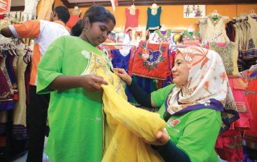 KANAK-KANAK dari Philea Home memilih pakaian dan aksesori untuk digayakan ketika Deepavali sambil dibantu sukarelawan F&N Beverages.