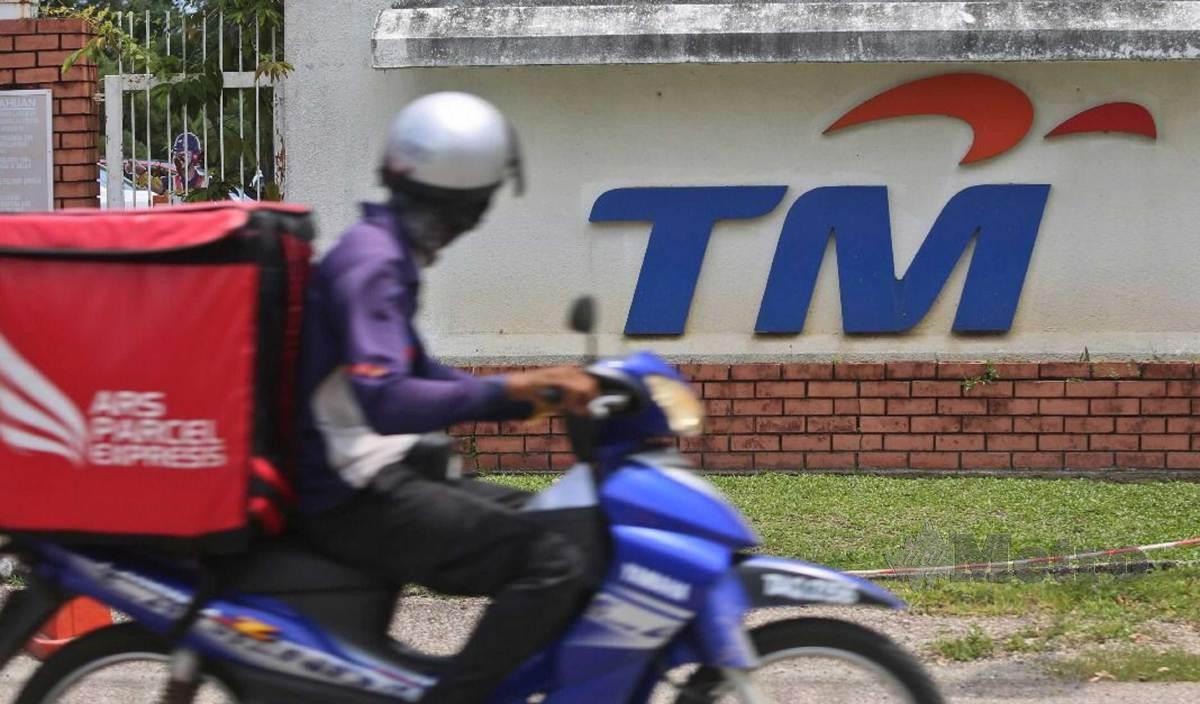 KELIHATAN seorang penunggang motosikal memakai pelitup muka melintasi papan tanda bangunan Telekom Malaysia (TM) Kuala Terengganu. FOTO Ghazali Kori