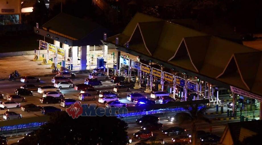 Antara kumpulan kenderaan yang melalui Plaza Tol Sungai Rasau selepas kutipan tol ditamatkan pada 12 tengah malam tadi. - Foto MUHAMMAD SULAIMAN