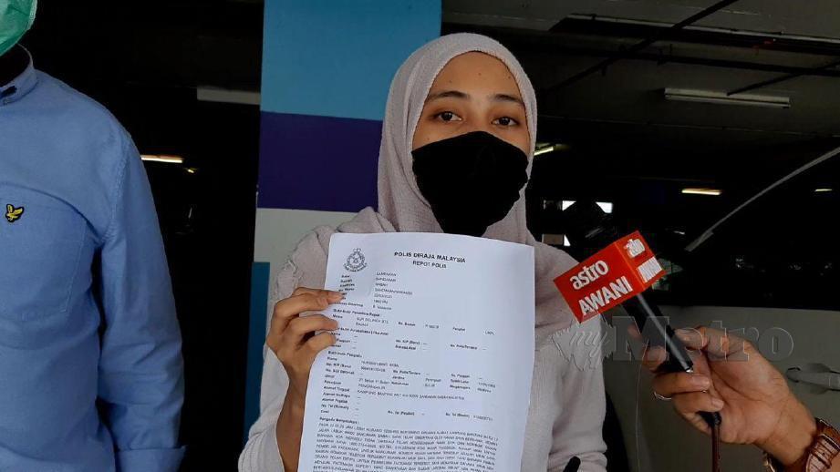 NURISAH menunjukkan laporan polis yang dibuat. FOTO Hazsyah Abdul Rahman