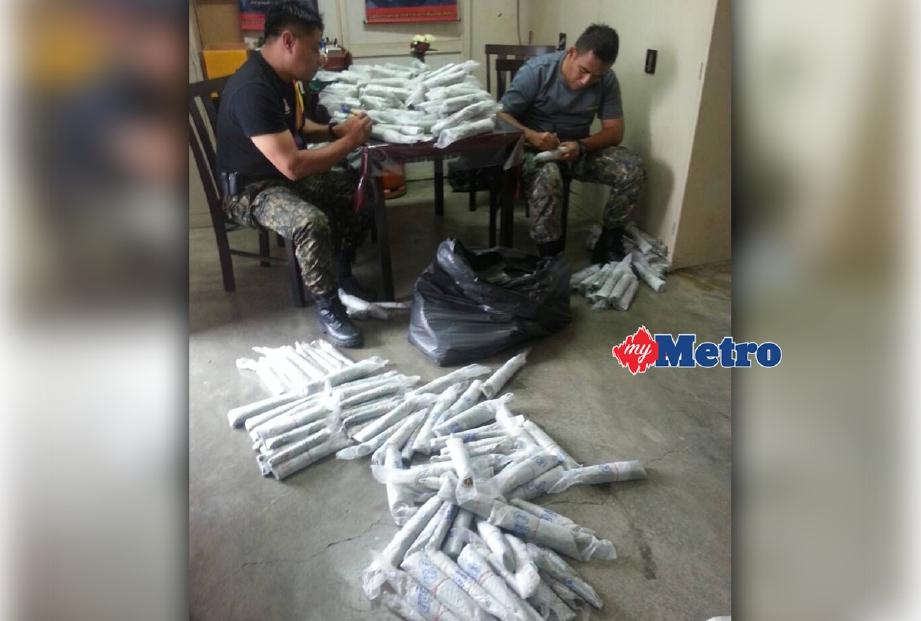 Anggota Agensi Kawalan Sempadan Malaysia (AKSEM) memeriksa daun ketum yang dirampas daripada seorang lelaki Thailand di Pengkalan Hulu. - Foto IHSAN AKSEM