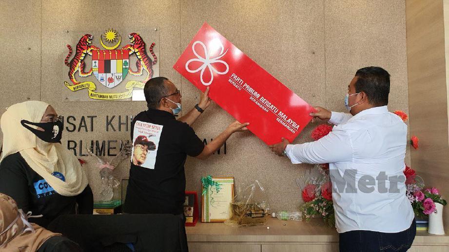 SHUKOR (kiri) dan Zamree menurunkan papan tanda parti. FOTO Hamzah Osman