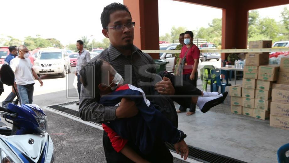 Pelajar lelaki diangkat untuk mendapatkan rawatan selepas terhidu gas kimia. FOTO Mohd Azren Jamaludin