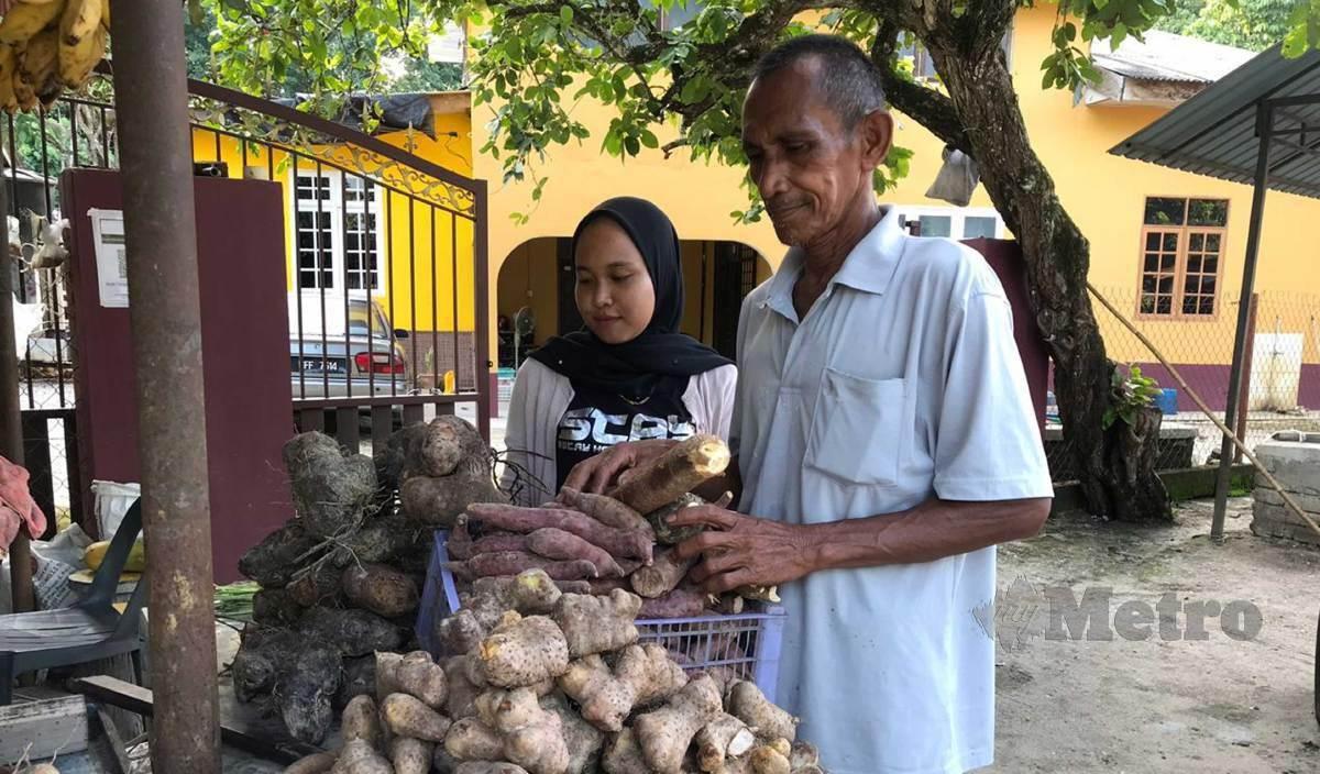 SAAD (kanan) dibantu anak bongsunya, Nurul Izza menjual ubi bagi memenuhi permintaan pelanggan ketika di temui di Kampung Kedai Piah, Ketereh. FOTO Hazira Ahmad Zaidi