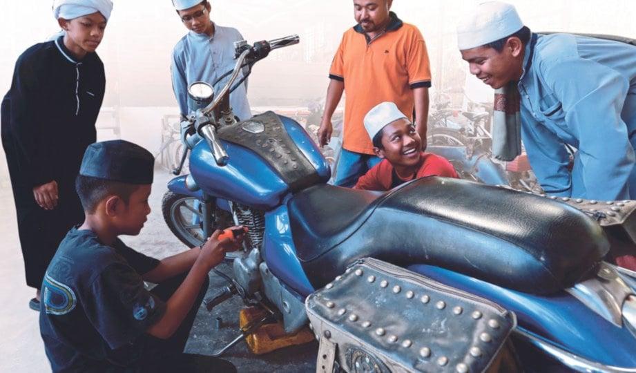 PELAJAR diajar kemahiran membaiki motosikal.