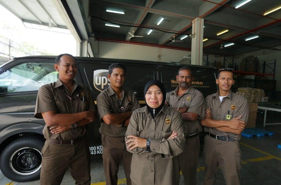 HASNIZA (tengah) bersama rakan sekerja.
