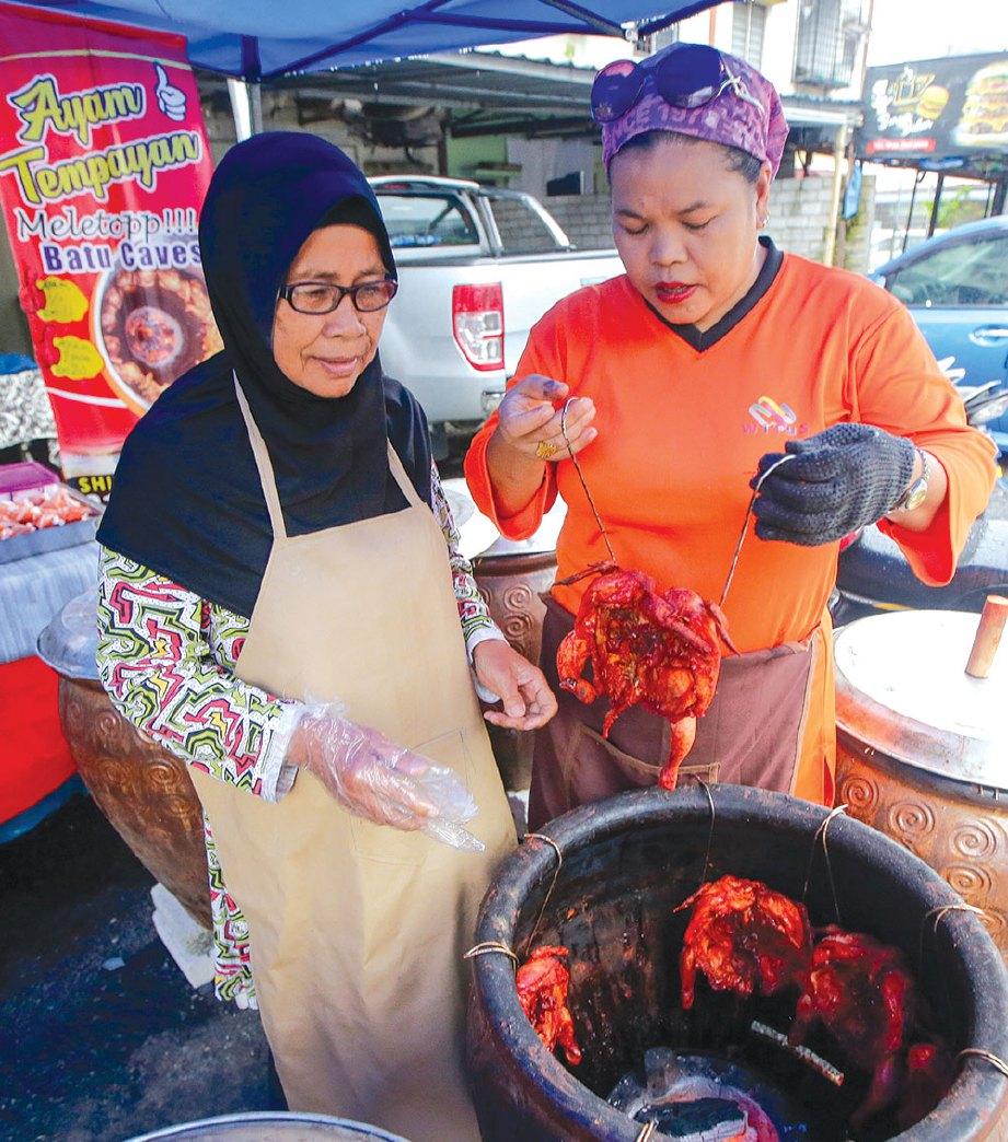 SHIELLA (kanan) membantu ahli Witus memasak ayam tempayan yang dijual sempena Ramadan lalu.