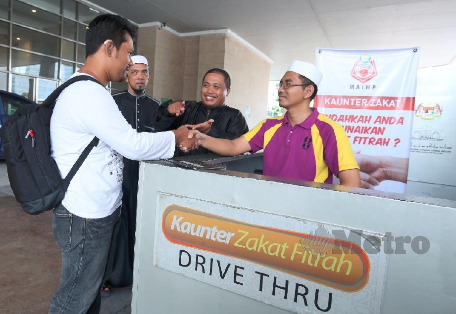 MOHD Amri (kiri) membayar zakat fitrah menggunakan bahasa isyarat kepada amil zakat, Mohd Khairul Ridhuan Mohd Fadzil (kanan) dengan dibantu Mohamad Zaid (dua dari kanan) di Kaunter Zakat Fitrah MTMZA, Putrajaya. FOTO Ahmad Irham Mohd Noor
