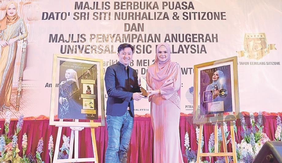 PENGARAH Urusan Universal Music Malaysia, SIngapura dan Indochina, Kenny Ong menyampaikan anugerah kepada Siti.